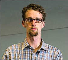 A photo of a young man with a goatee wearing a gingham shirt standing behind a podium.
