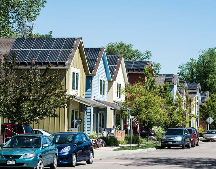 Neighborhood of houses with rooftop solar panels.