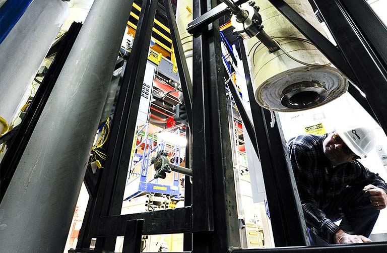 Photo of a man kneeling and looking underneath large testing equipment in an NREL facility.