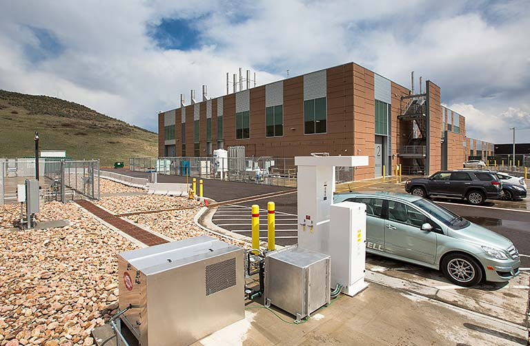 Photo of the Hydrogen Infrastructure Testing and Research Facility building, with hydrogen fueling station and fuel cell vehicles.