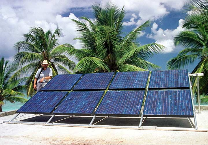 Photo of a solar photovoltaic module with palm trees and the ocean in the background.