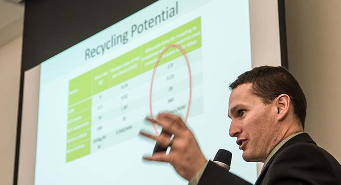 A man speaks into a microphone in front of a slide presentation on recycling potential.