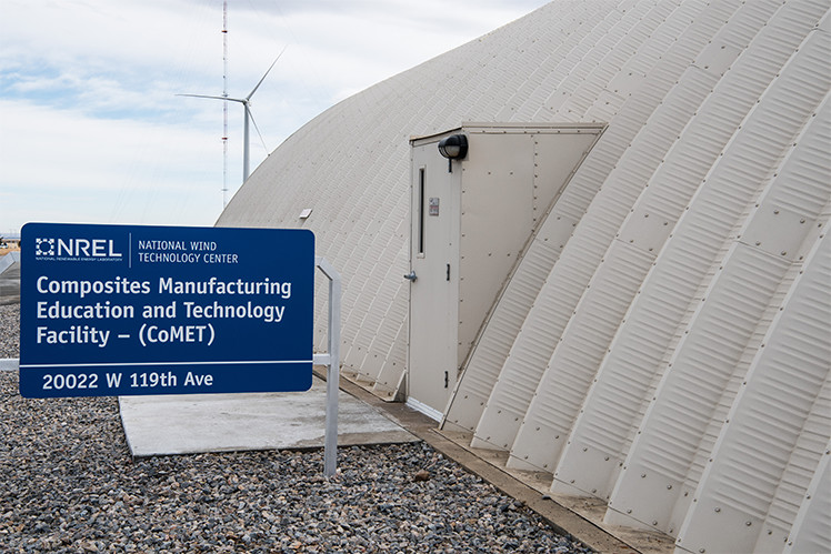 Photo of a white dome-shaped building with a sign that says, 'Composites Manufacturing Education and Technology Facility – (CoMET ),' and a wind turbine in the background.