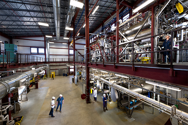Photo of a large, warehouse-like, lab space with several people in hard hats operating equipment.