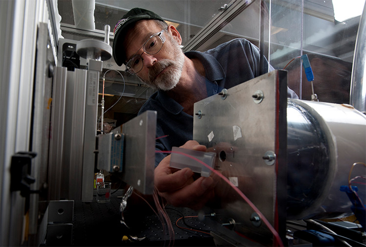 Photo of a man adjusting equipment in a lab, specifically an air-cooling test bench.