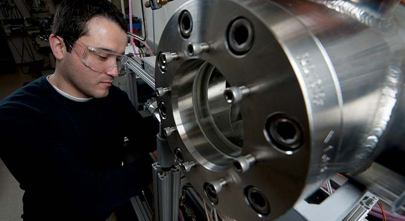 A researcher wearing protective eyewear works on a silver piece of machinery.