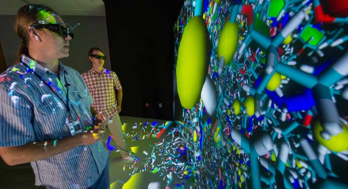 A photo of two researchers examining a colorful 3D molecular model.