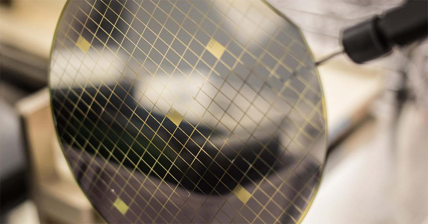 A translucent silicon wafer is at the foreground with a blurred background.