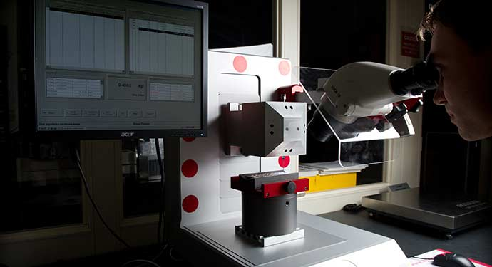 Researcher examines material using lab machinery.