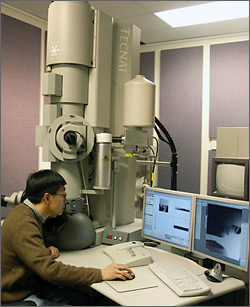 Photo of NREL researcher using transmission electron microscope.