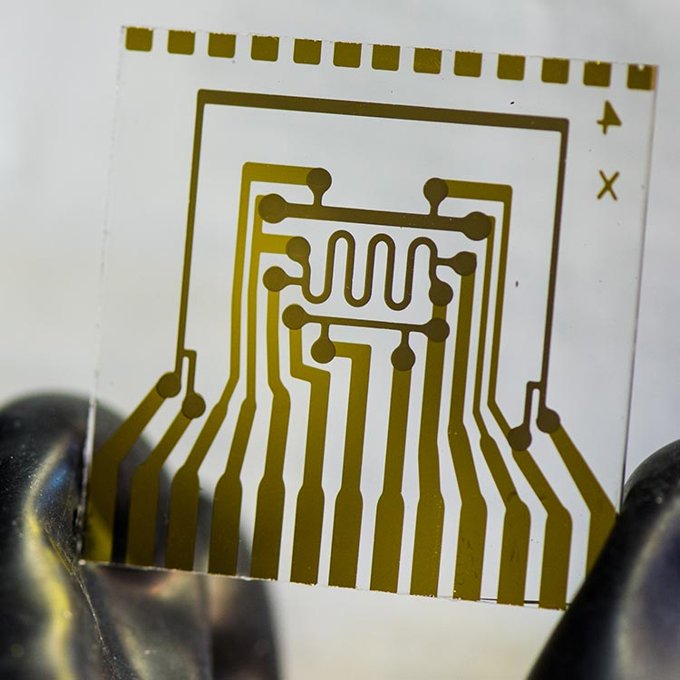 A photo of a glass square held between two fingers. The glass has a pattern of metal contacts that make up a special electrical circuit. This device represents an electrical calcium test glass card used to measure vapor-barrier permeation rates.