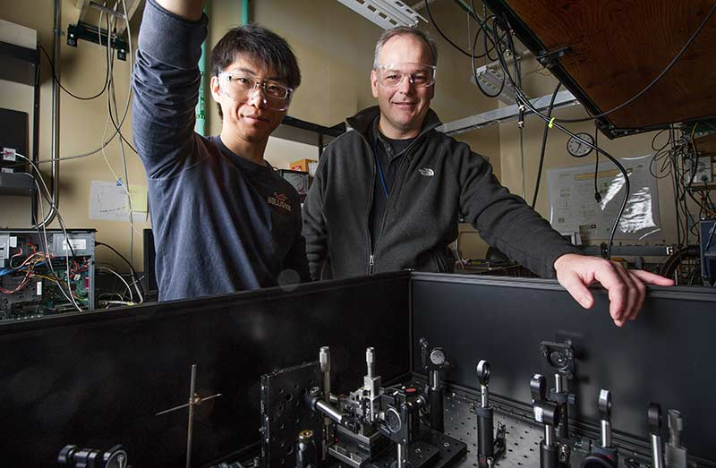 Two men stand behind a spectrometer at an NREL lab.