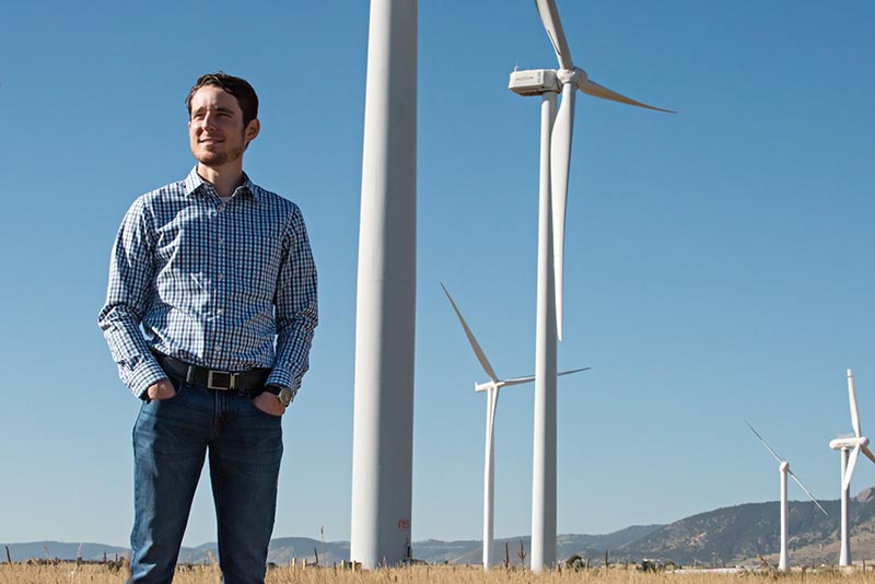 An NREL researcher stands near wind turbines at the National Wind Technology Center.