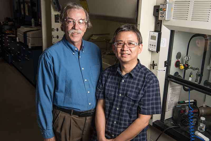 Photo of two men in a lab.