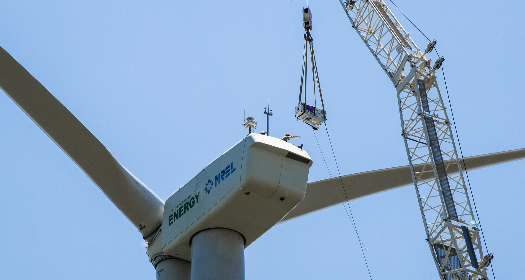 Photo of the top of a turbine and a crane lowering a piece of hardware onto the nacelle.