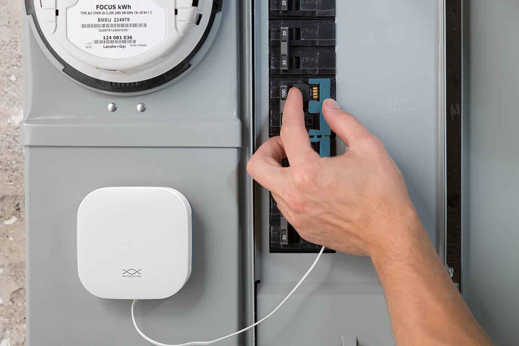 A close-up photo of hands attaching a wire to a circuit box.