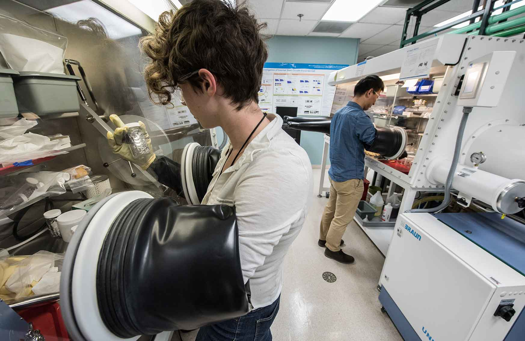 Two researchers using glove boxes in energy storage laboratory.