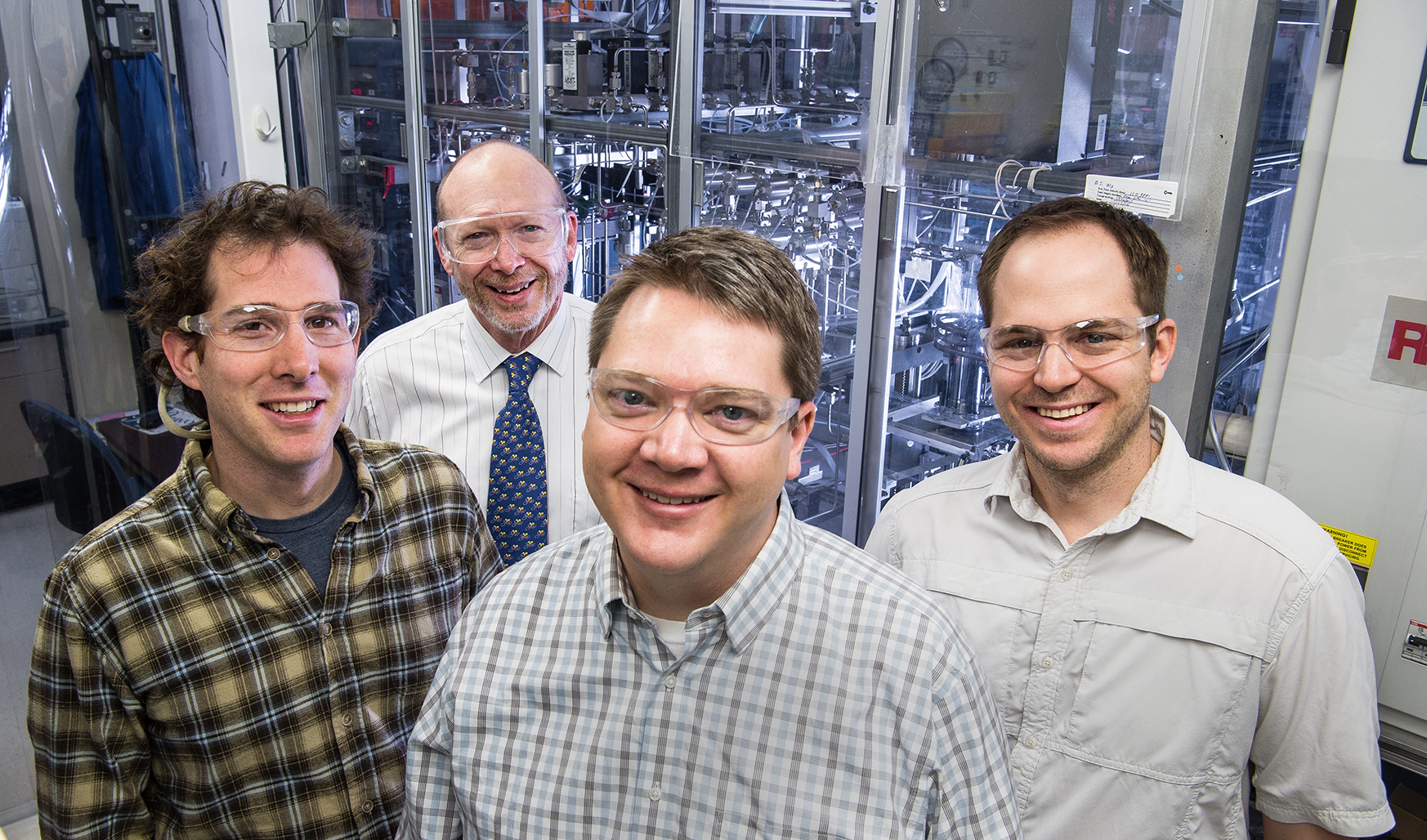 Four men stand in a laboratory at the National Renewable Energy Laboratory.