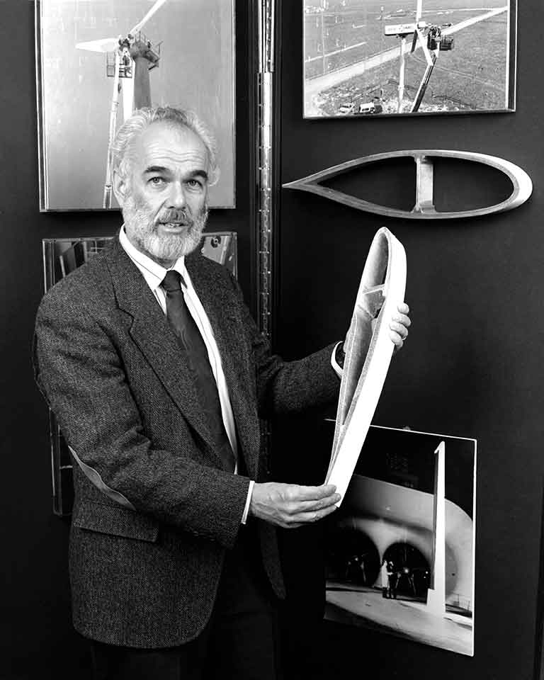A man holds a model of a section of a wind turbine foil.