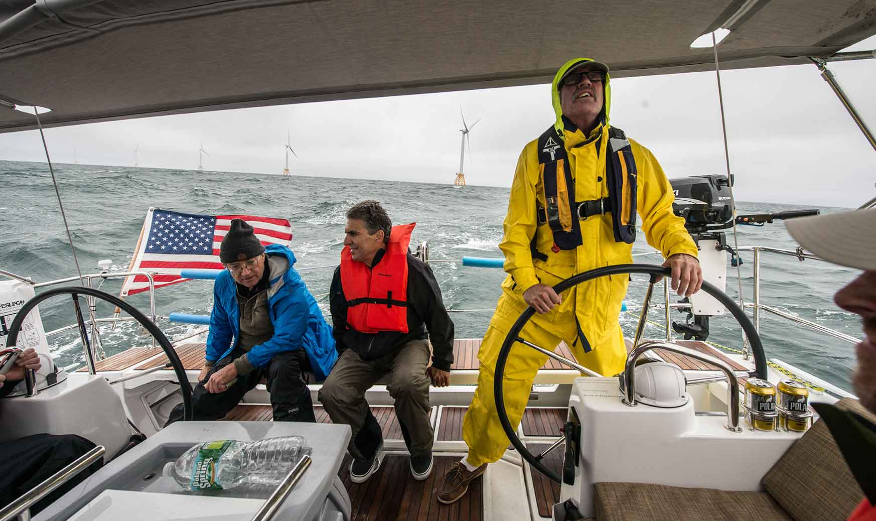 Three men on a boat in rough waters. Two in the background are looking at an offshore wind farm while one in the foreground is steering the boat.