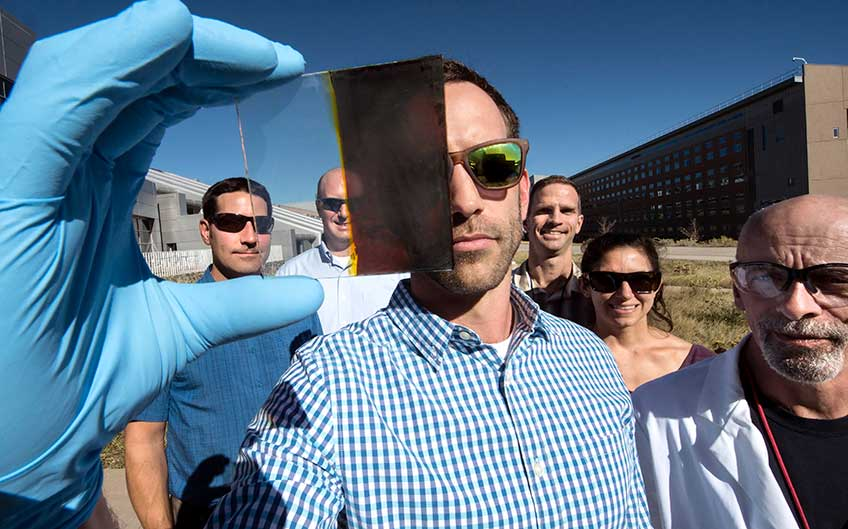 A man holds a small solar cell, with four men and a woman behind him outdoors.