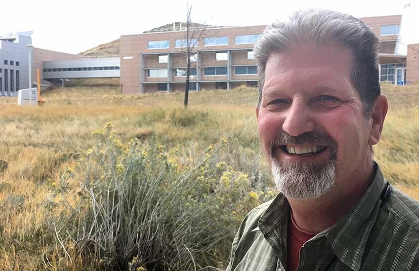 Photo of a man standing at the base of a hill covered by long brown and green grasses, topped by a large modern facility.