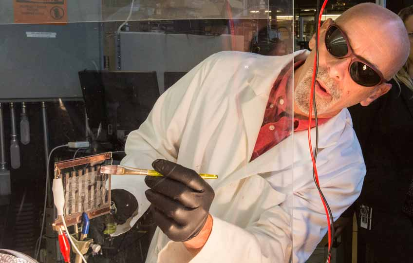 A man paints perovskites onto a piece of glass, creating a solar cell.