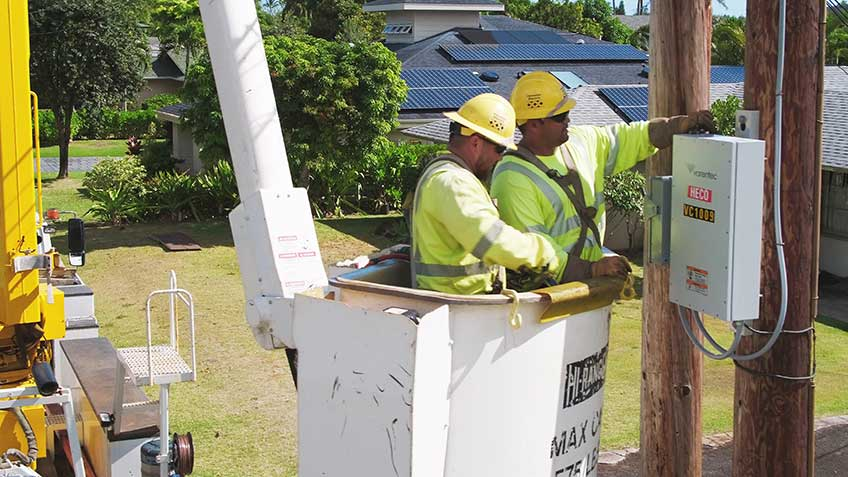 Photo of two men in yellow hard hats installing electrical equipment on a telephone pole.
