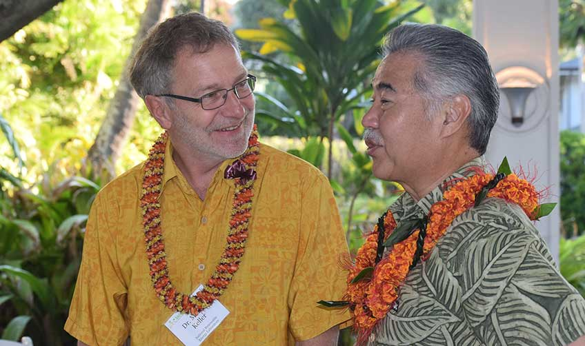 Photo of two men wearing Hawaiian shirts and flower leis.