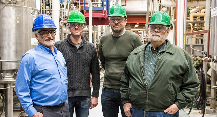 Four men stand in front of equipment in a lab at NREL.