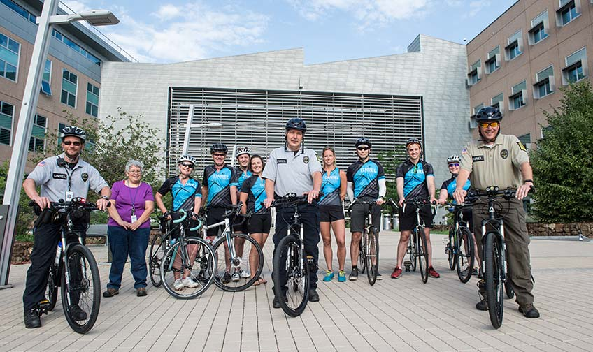 A group of cyclists, some with blue jerseys and some with security uniforms, stand with their bikes in front of a modern building