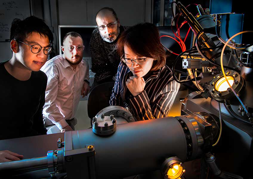 Three men and a woman look at machinery in a lab.