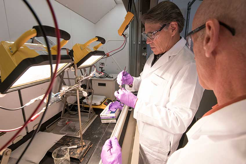 Energy Secretary Rick Perry uses a small paintbrush to make a solar cell.