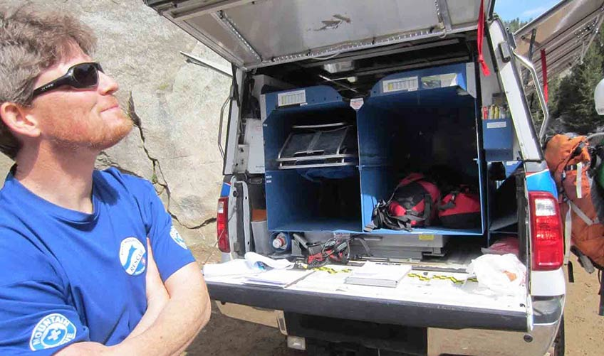 A man stands near an emergency vehicle outdoors.