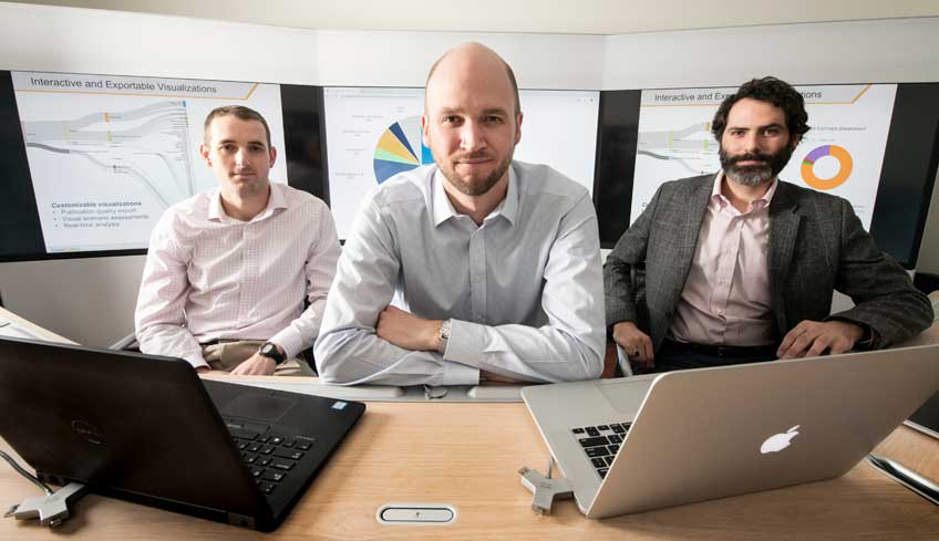 Three men sit at a desk with two laptops in front of them.