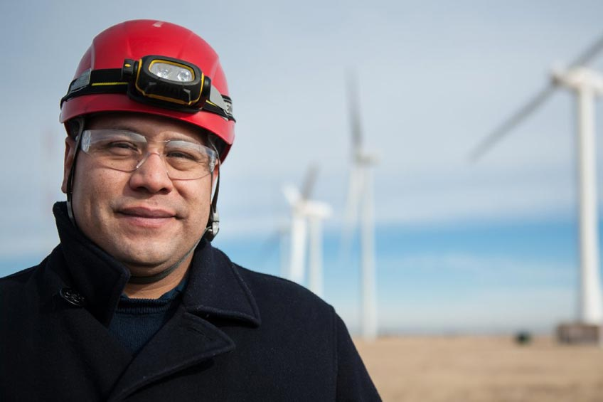 A man in a helmet stands in front of wind turbines.