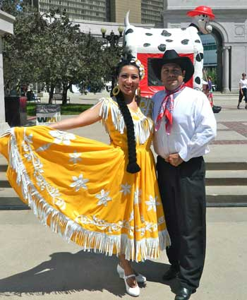 A man and a woman in Mexican costumes strike a pose outdoors.