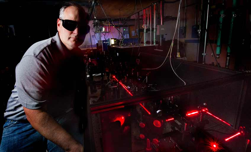 Photo of a man in a dark laboratory sitting next to a red laser beam.