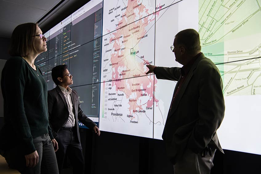 Three researchers view data on a large computer screen.