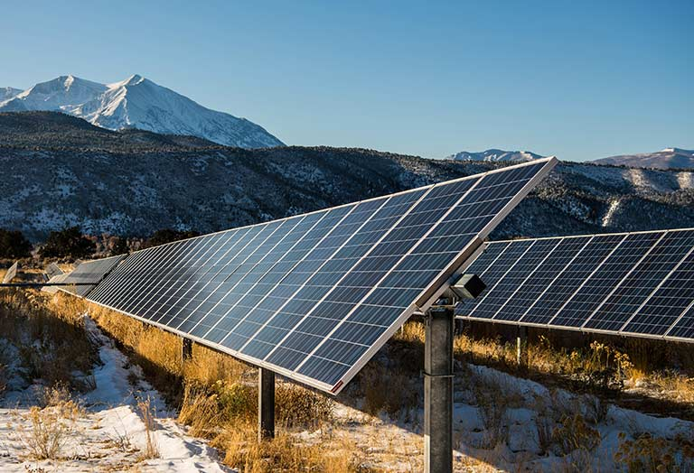 An array of solar panels in front of a snow capped mountain.