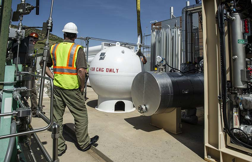 Crews install a large round storage vessel for natural gas.
