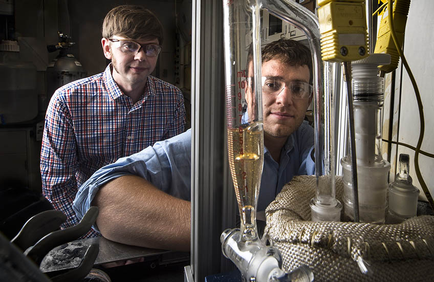Two researchers working with scientific equipment in the lab.