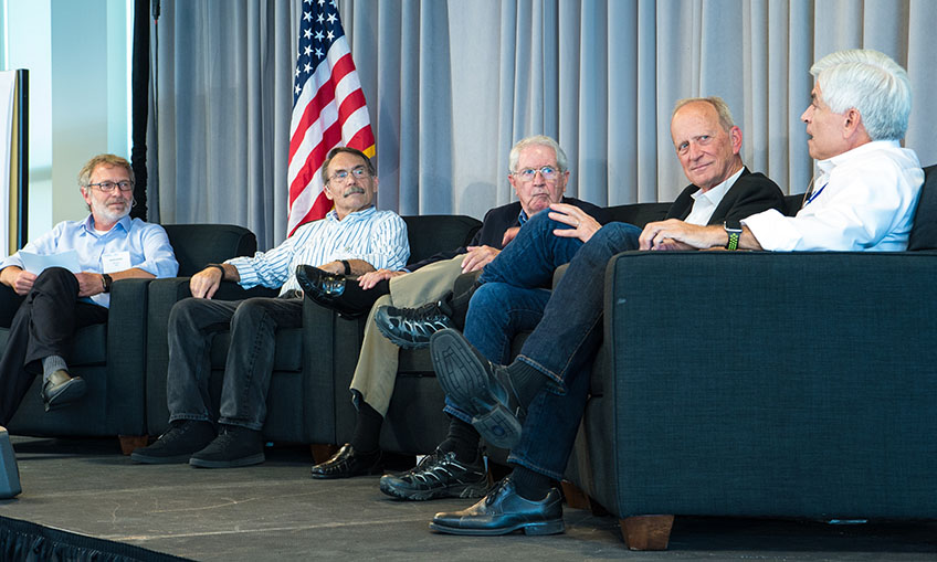 Five men sit on a stage talking