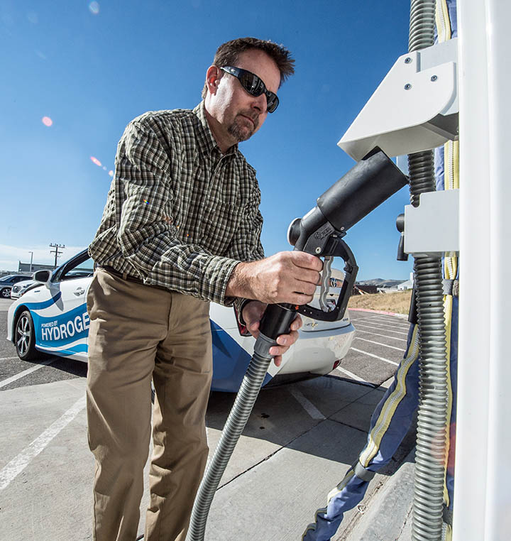 A man grips the handle of a hydrogen fueling nozzle.