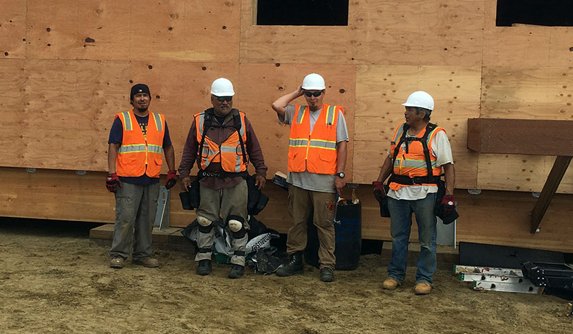 Four men wearing construction gear stand together on a worksite