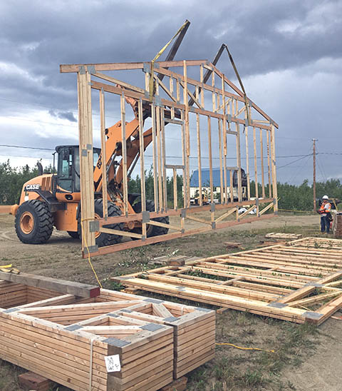 A crane lifts a truss for the wall of a home