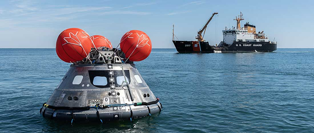 The spacecraft is right-side up as a U.S. Coast Guard boat floats behind it.