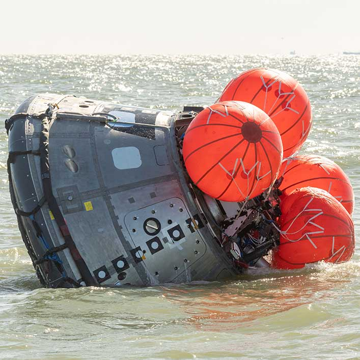 A spacecraft undergoing tests In the ocean. The ship is partially submerged.
