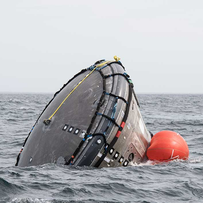 Closeup of the spacecraft that is almost upside down in the water.