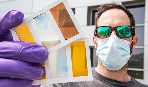 A man holds a prototype of a perovskite window that shows several different colors.